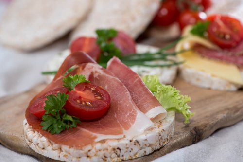 Rice cakes with fresh ham, tomatoes and coriander