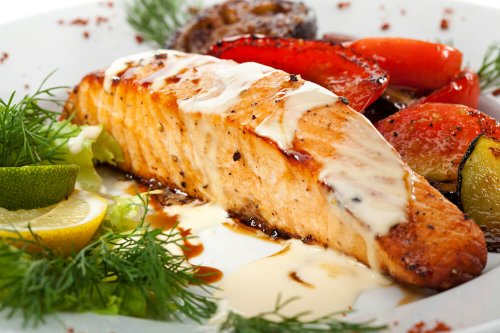 Salmon with grilled vegetables, white sauce and lemon